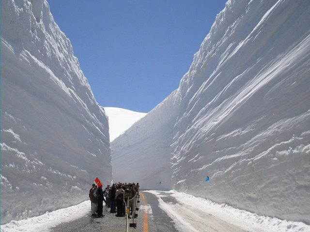 [【2泊5食付バスツアー】 立山 雪の大谷ウォーク {4月限定}] 人がこんなに小さく写るほど高い雪の壁。雪の大谷